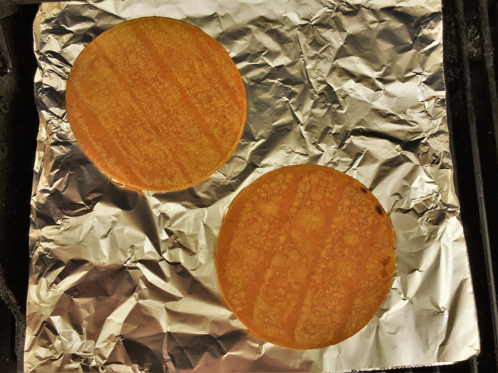 Tortillas warming on aluminum foil on the grill.