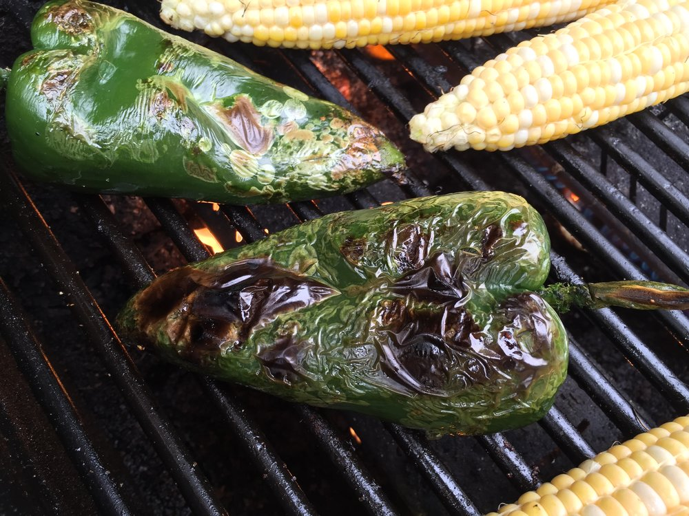 Poblano chiles roasting alongside ears of corn on the Adventure Kitchen grill.