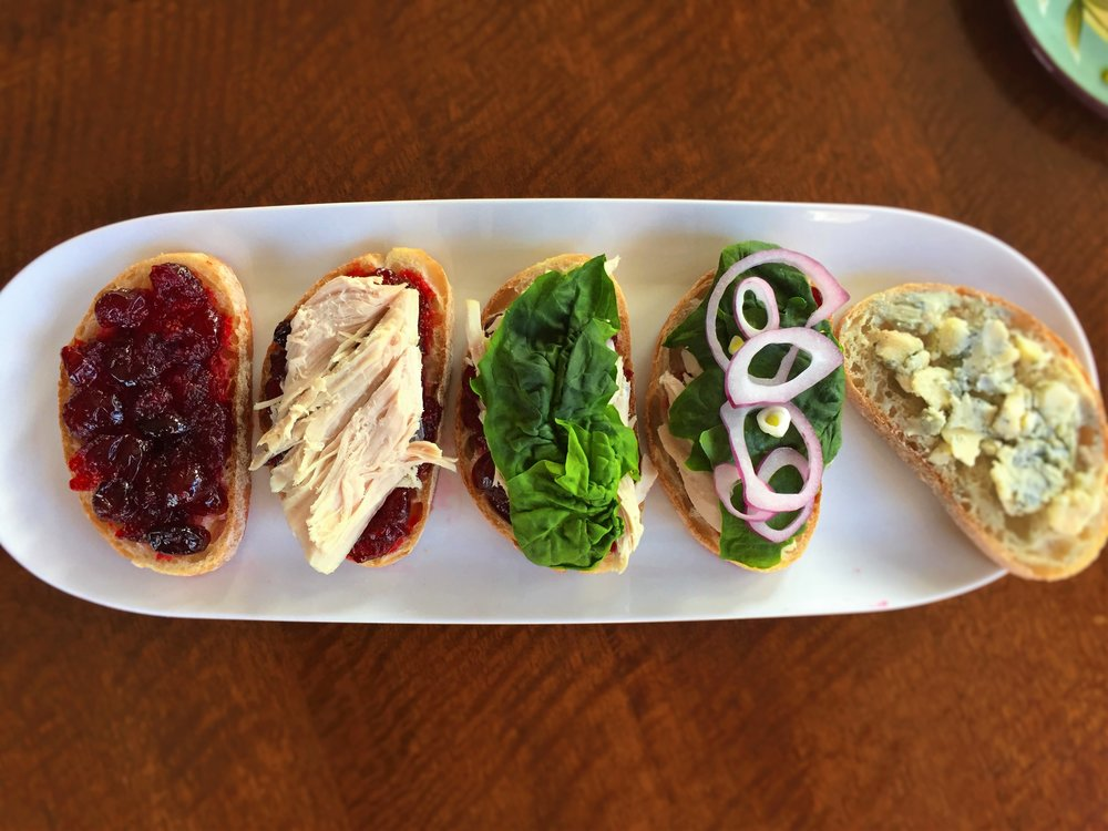 All the layers of our Cranberry-Bleu Turkey Sandwich: cranberry sauce, turkey, spinach leaves, red onion, gorgonzola cheese.