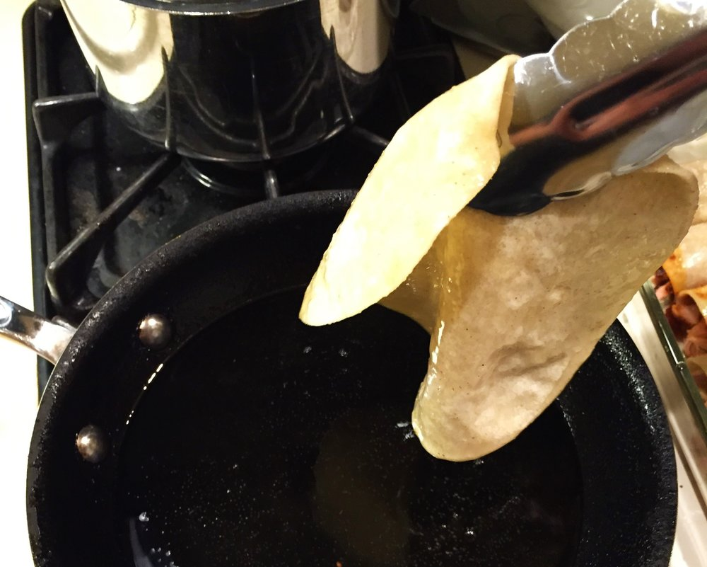 Removing the tortilla when it has softened in the oil, but before it becomes crisp