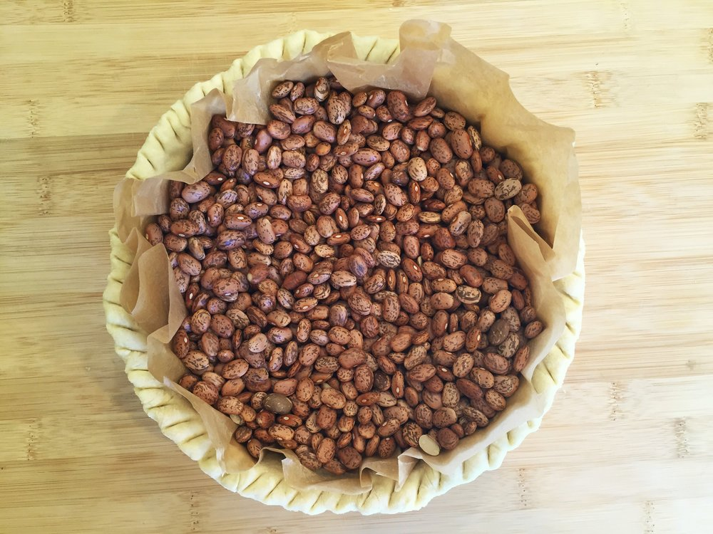 Beans are used as a weight to pre-bake a parchment-lined pie crust.