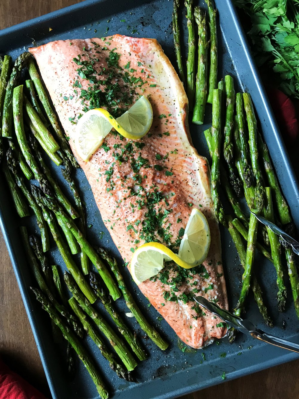 It's a sheet pan dinner that helps you clean the pan at the end! (Plus, yum.) Sheet Pan Lemony Garlic Salmon with Asparagus, made in the Adventure Kitchen.
