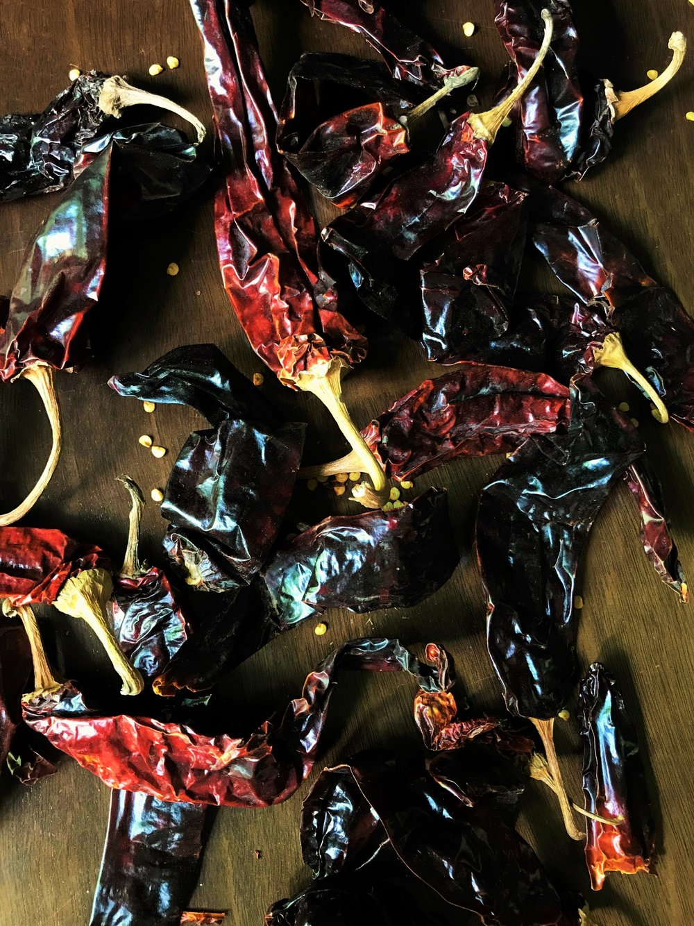 These are dried guajillo chiles in my kitchen. They're usually a deep burgundy color, but can sometimes range into a lighter shade. If they're still fairly fresh when you buy them, they should be somewhat pliable, like leather. If they're older and brittle, you can still use them; you'll just toast them in whatever pieces they break into as you work.