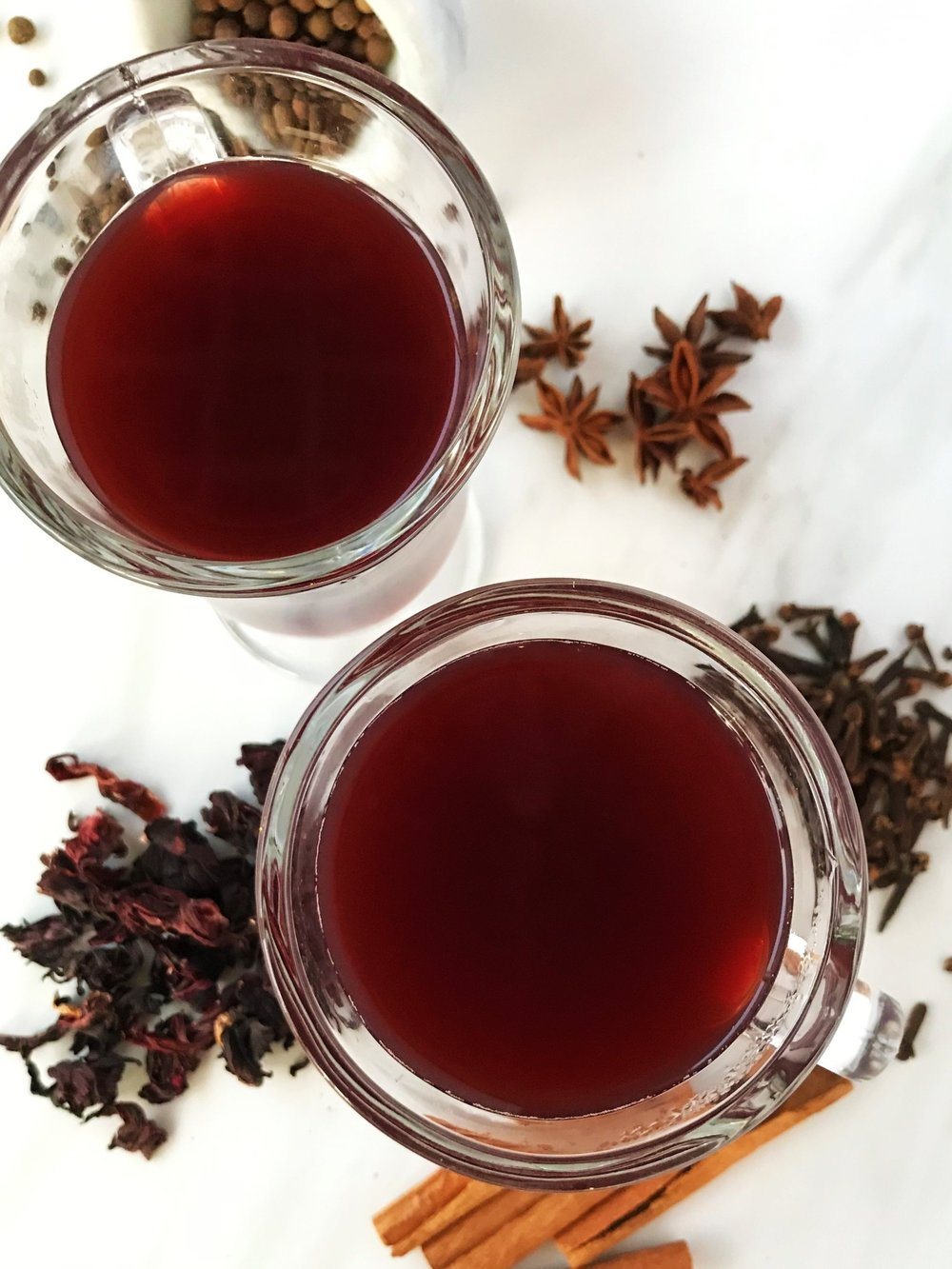 Hibiscus Mulled Cider photographed in our Adventure Kitchen Pop-Up Spice Shop. We infuse apple cider with hibiscus flowers and classic mulling spices for a warm and tasty drink on a cold day.