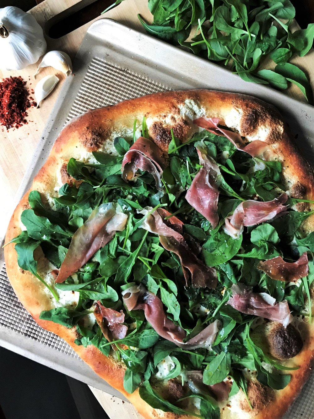 """Arugula and Prosciutto Pizza with Aleppo pepper made in the Adventure Kitchen. (Um, I call this crust shape """"rustic.""""I"""