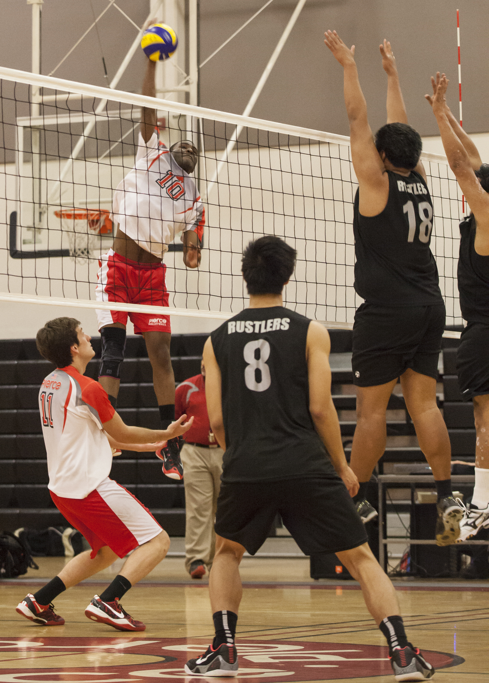Corey Pitt spikes the ball against two Golden West defenders during a match against Golden West College on Wednesday Feb. 18. Pierce would go on to win the match in straight sets, 3-0. Woodland Hills, Calif.   Full story
