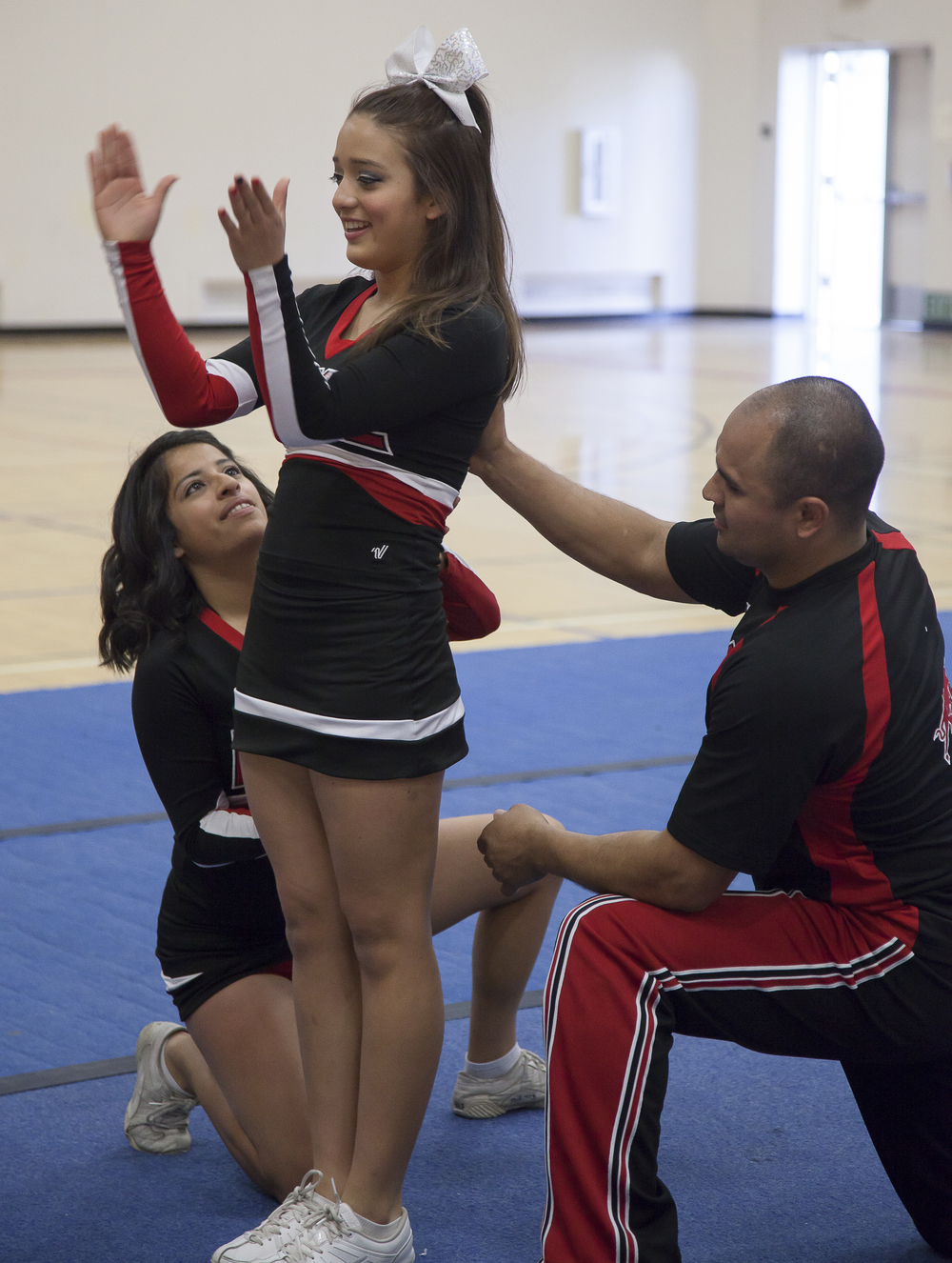 Dulce Rendon, left, and Julio Alanya, right, prepare to catch Vivian Herrera, center, during practice inside the North Gym on Sunday March 1, 2015. Woodland Hills, Calif.  Read the full story here
