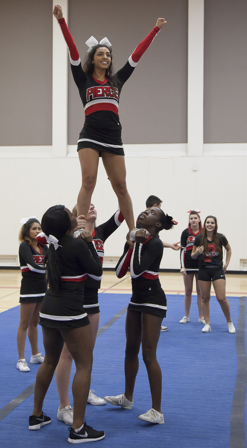 Amanda Perez, top, is lifted by fellow team members while other members watch inside the North Gym on Sunday March 1, 2015. Woodland Hills, Calif.  Read the full story here