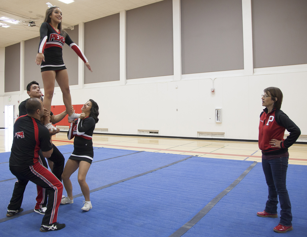 "Coach Jenny Ghiglia watches as members of the Pierce Cheer Competition team perform a maneuver called a ""full up"" during a practice session in the North Gym on Sunday March 1, 2015. Woodland Hills, Calif.  Read the full story  here"