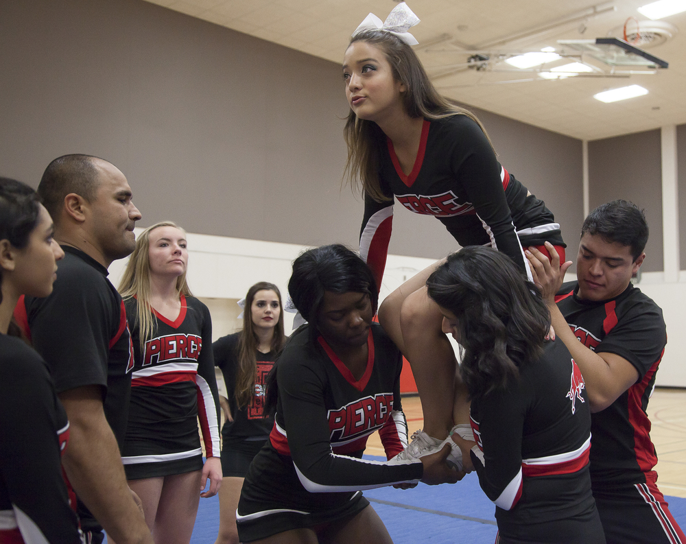 """Vivian Herrera prepares to be lifted by Karlanda Duquesnay, Dulce Rendon and Jesus Guzman in a maneuver called a """"full up"""", as other team members watch during a pracitice session in the North Gym on Sunday March 1, 2015. Woodland Hills, Calif.  Read the full story  here"""