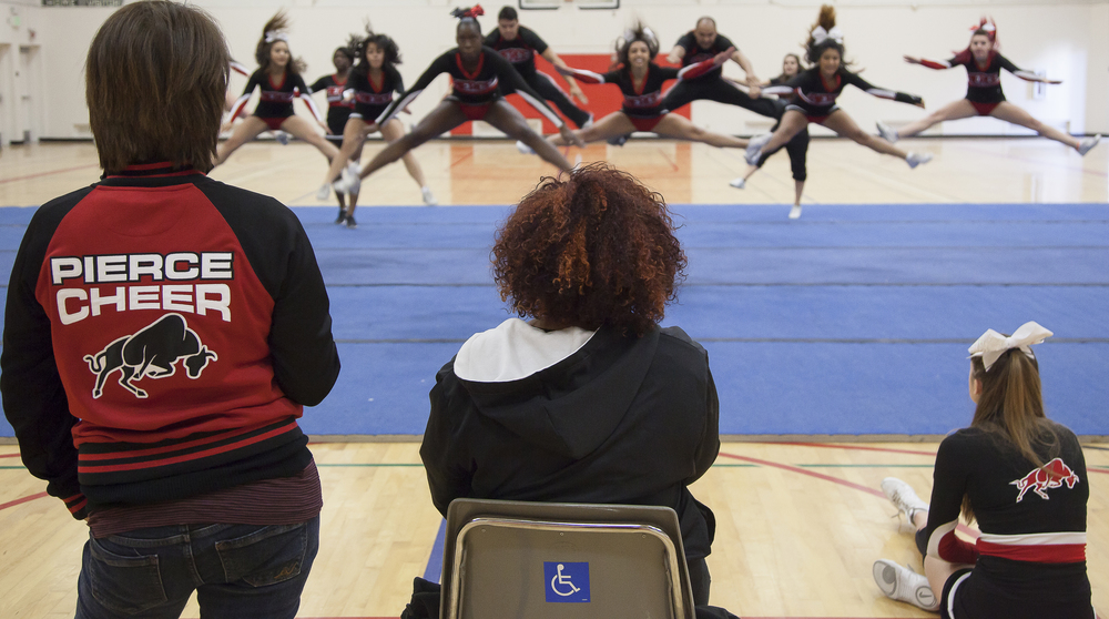 From left to right: Coach Jenny Ghiglia, Jordyn Lett and Katie Kucera watch as other members perform their routine inside the North Gym of Pierce College on Sunday March 1, 2015. Woodland Hills, Calif.  Read the full story here