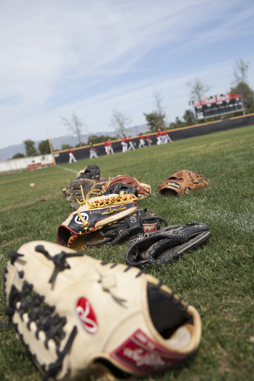 Gloves lay on the grassas the team practices in the background at Joe Kelly Field on Tuesday, March 10, 2015. Woodland Hills, Calif.  Read the full story here