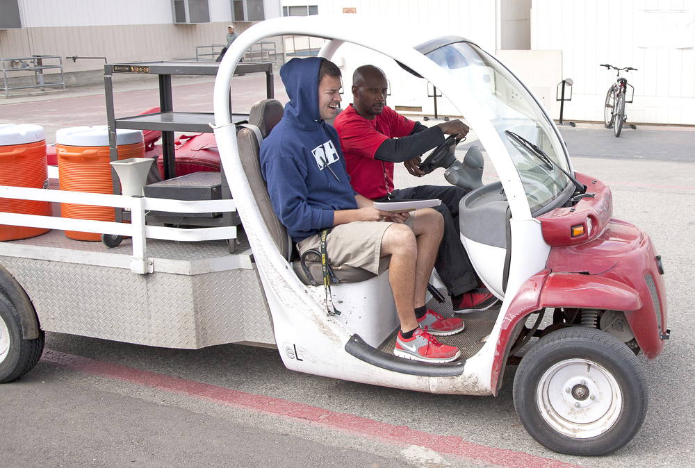 Alejandro Cerda rides in a cart loaded with equipment driven by defensive co-ordinator Torry Hughes for a spring practice and training session on Thursday, May 21, 2015. Woodland Hills, Calif.