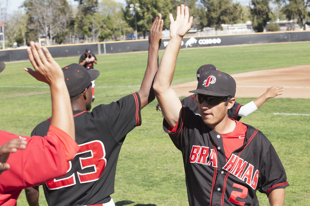 Jordan Abushahla, right, receives high fives from teammates as he walks to the dugout after the top of the first inning in a home game against Glendale College in Woodland Hills, Calif. on Saturday, Feb. 13, 2016.