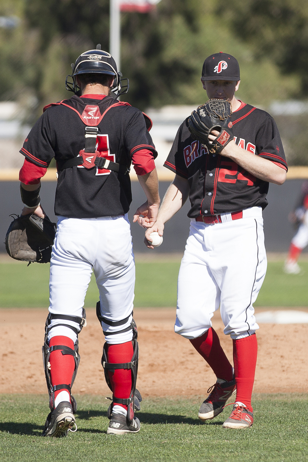 Evan Yeager, left, has a brief meeting with Brett Weisberg on the mound before facing the next Glendale batter during a home game in Woodland Hills, Calif., against Glendale College on Saturday, Feb. 13, 2016.