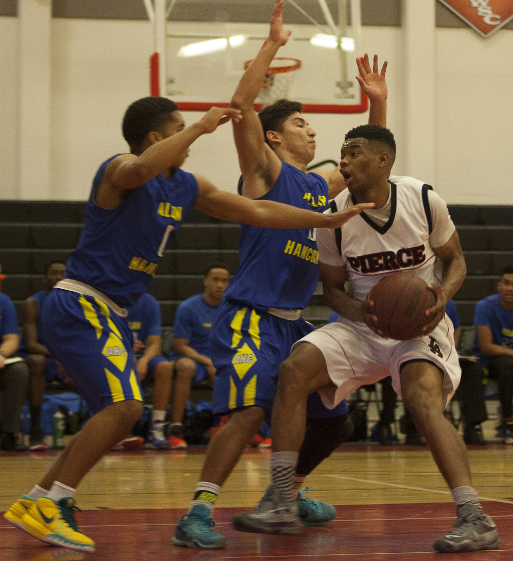 Kaelan Hicks, right, goes up against two Hancock players during a home game against Allan Hancock on Saturday, Feb. 13, 2016 in Woodland Hills, Calif. Pierce would win the game in overtime, 95-91.