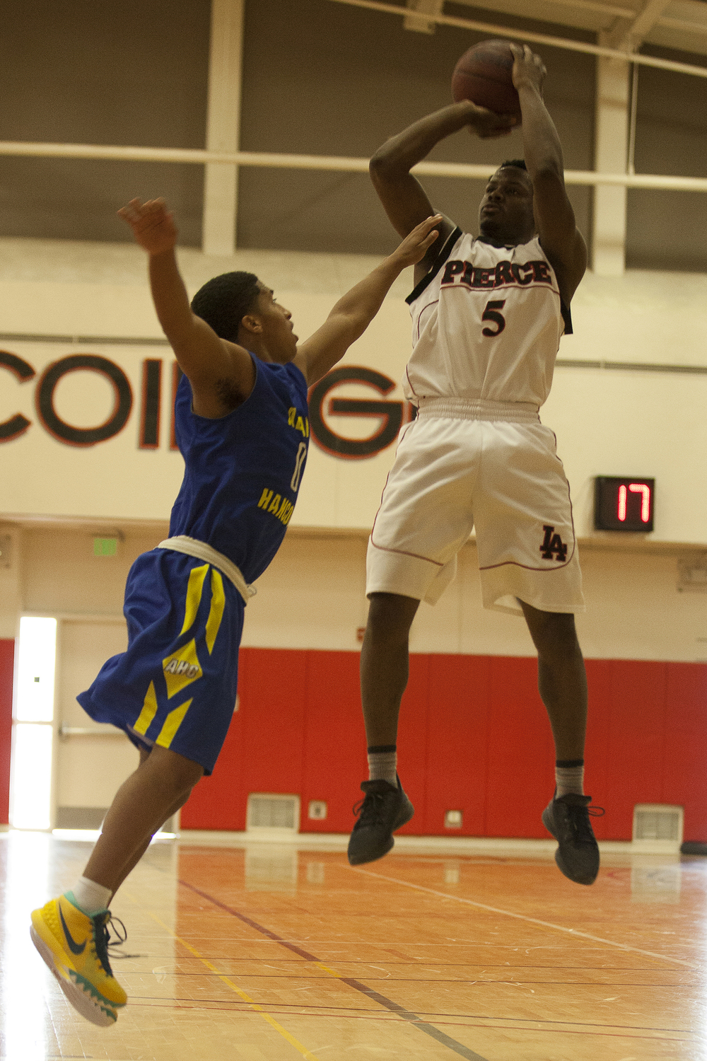 Hancock guard Shane Carney tries to block a jump shot by Montel Shirley in a game on Saturday, Feb. 13, 2016 in Woodland Hills, Calif.
