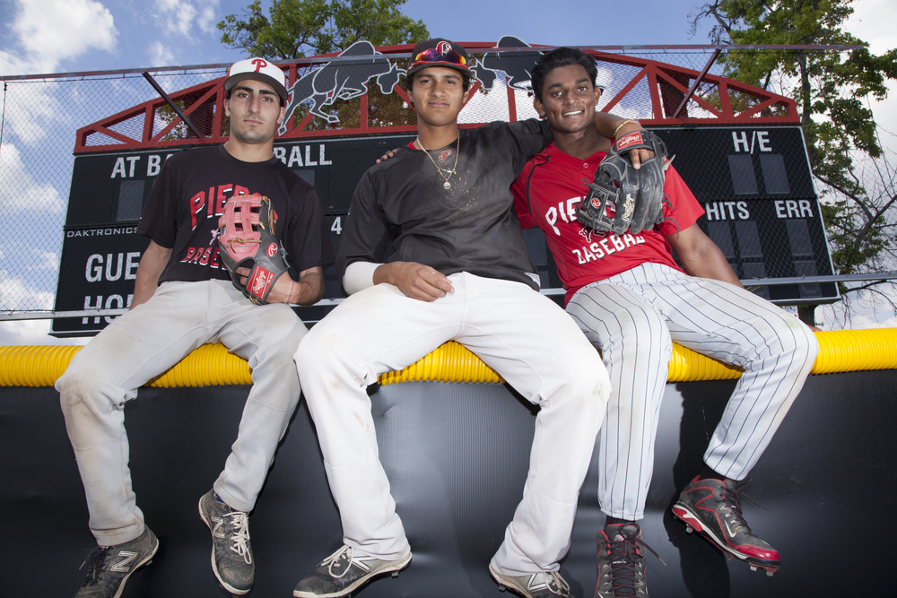 Trevor Dergazarian, Edgar Vela and Deion Fernando sit on top of the outfield wall of Joe Kelly Field in Woodland Hills, Calif. on Monday, April 11, 2016.