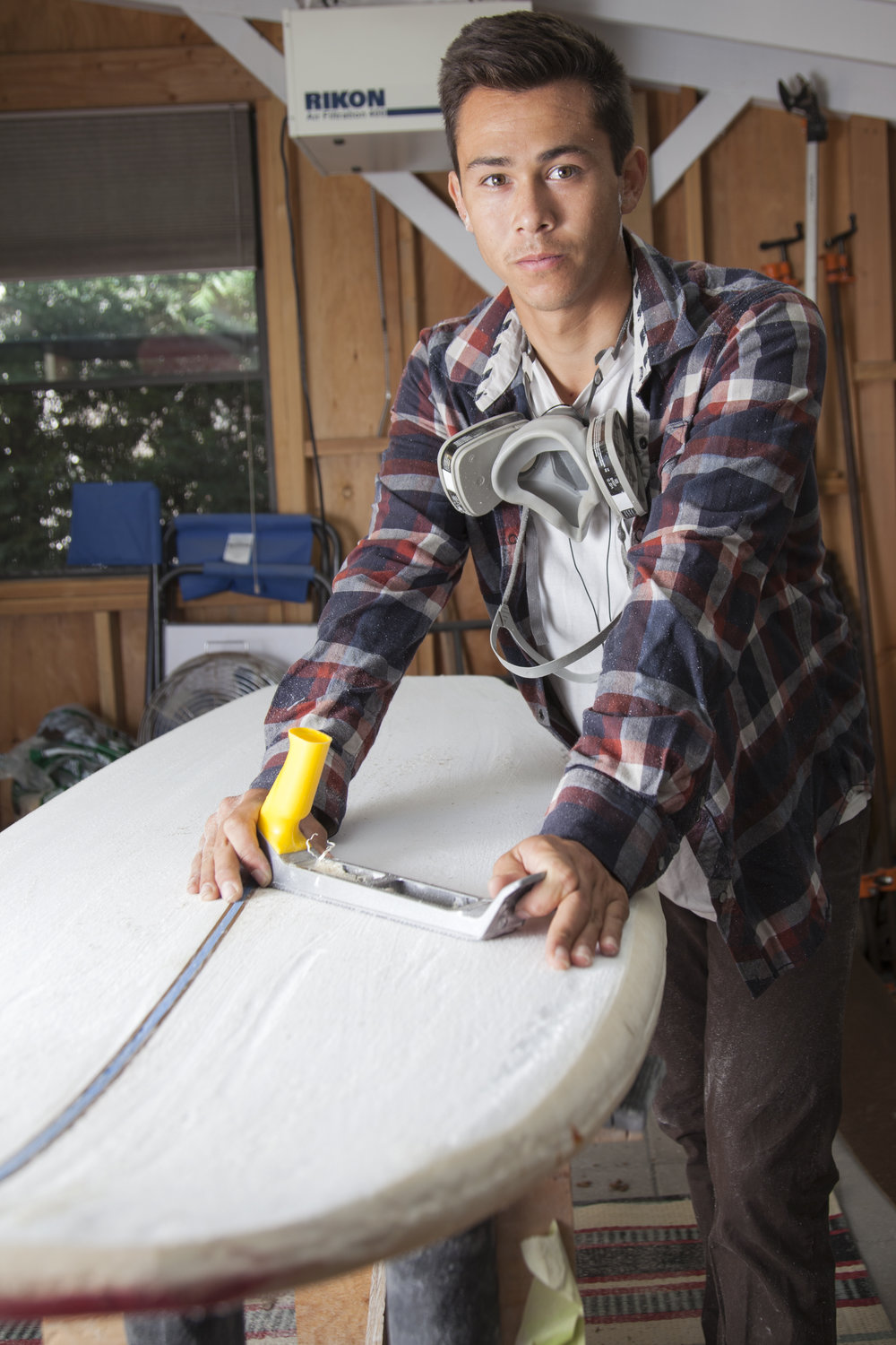 Kieran Giffen works on a custom surfboard inside his workshop in the back yard of his home in Woodland Hills, Calif. on Tuesday, Oct. 4, 2016. Giffen began shaping custom surfboards for his friends when he was 13, but now Giffen receives offers from clients who find him on social media.  Read Giffen's full story   here  .