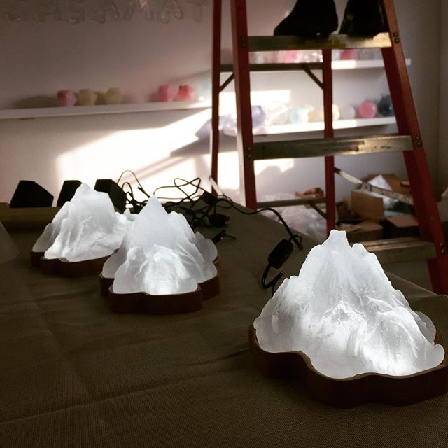 Mountain time and a view of our messy studio as we set up for the Crawl.  These cute little solid cast glass mountain look nice lit on their maple wood based. • • • • • • #mountains #mountain #glass #lighting #lightingdesign #decor #interiordesign #architecture #art #craft #vancouver #solidglass #glassart #handmade #maker #contemporaryart #canadiandesigner #maple #homedecor #light  #eastsideculturecrawl