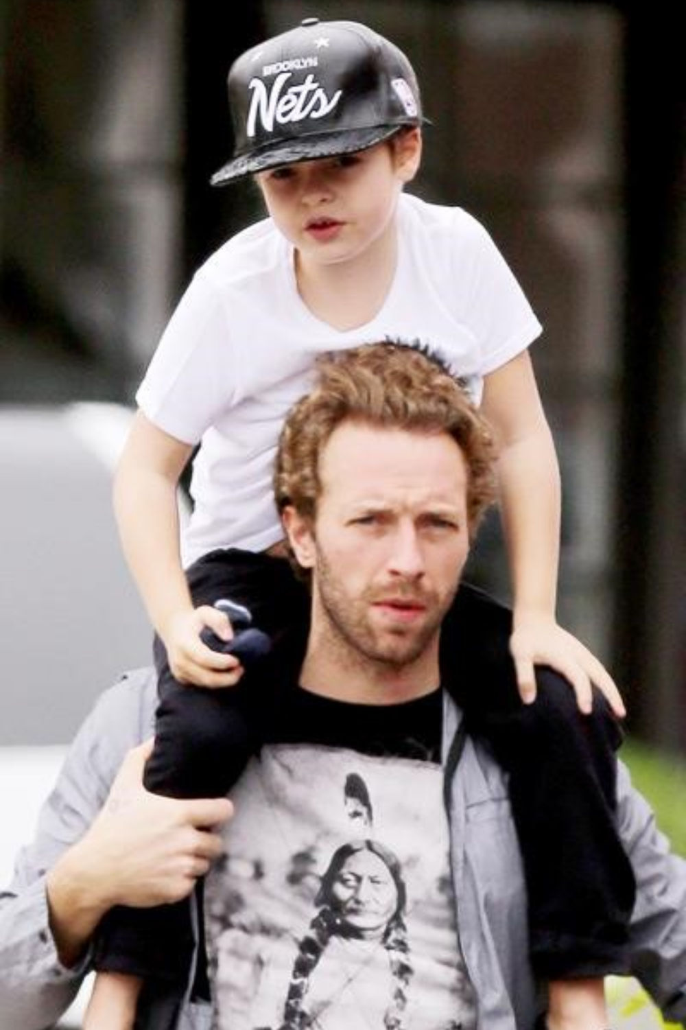 Style on point! Moses chills out with a snapback- cap atop his father's shoulders
