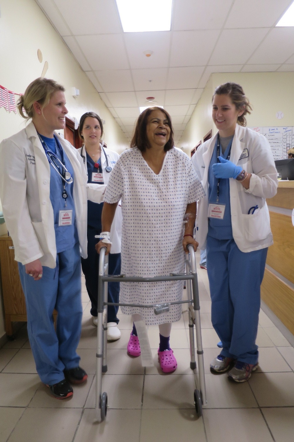 Carolyn Beagan, DPT (left) and Nicole Durand, DPT (right) help a patient ambulate who had both knees replaced 24 hours previously