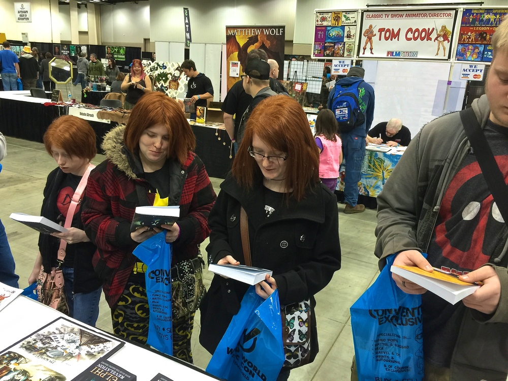Teens at the Indianapolis Comic Con checking out paperbacks of The Delphi Trilogy and Seti's Charm.