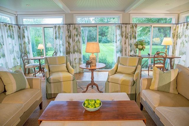 In the family room, our client's antique books add texture and coziness to a room that is otherwise glass on three sides. Green and white hydrangea blossoms printed on drapery linen help soften the strong light of a summer day. Happy green stripes and earth-toned European linens recall our client's beautiful gardens. Ottoman is custom design Karen Beckwith Creative and crafted by @jkcustomfurniture  Throw pillows are custom Karen Beckwith Creative using fabric by @osborneandlittle  Draperies are custom Karen Beckwith Creative using linen @ninacampbellltd for Osborne & Little Rug is custom Karen Beckwith Creative Sofas and chairs are custom Karen Beckwith Creative using fabric by Osborne & Little and @schumacher1889 Photographer: @scottbarrowphotography  #karenbeckwithcreative #interiordesign #interiordesigner