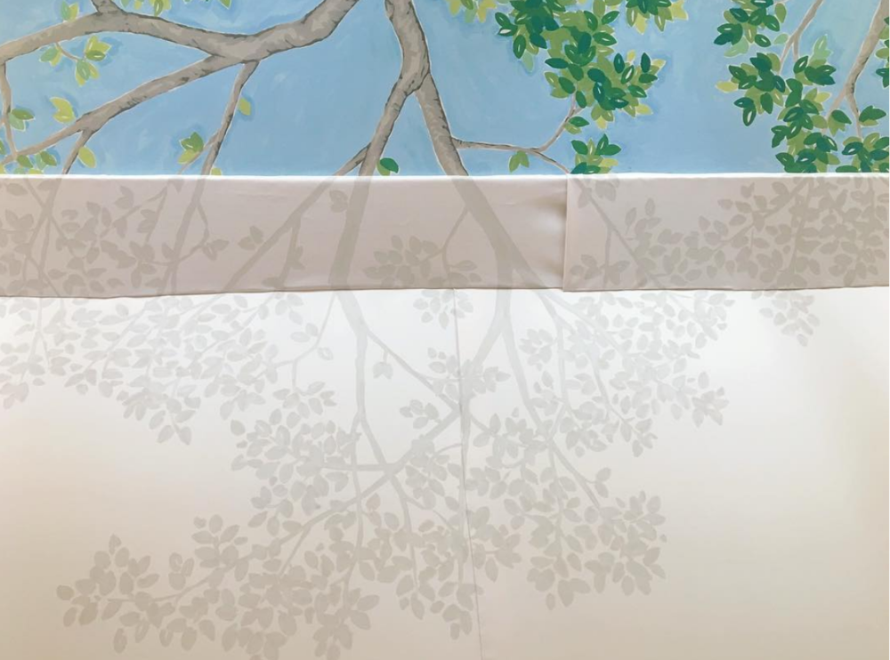 At the intersection of where the tree grows beyond the tent and the branches continue,  Art & Atmosphere  completed the trompe-l'oeil effect by painting the shadow of the leaves and branches onto the canvas duck. This supports the illusion that the tree is much larger than the room.