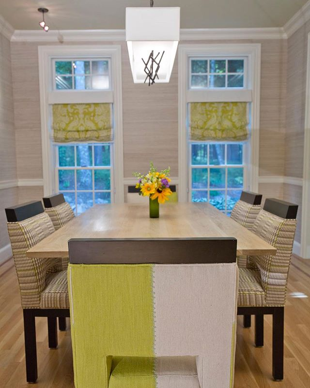 """Our goal for the dining room was to make a relatively small room feel larger by keeping the color palette light and airy. The combination of upholstery fabric on our custom chairs is playful but still sophisticated. Our client requested that our color scheme work with many different kinds of """"holiday"""" table settings. By keeping the room neutral with an accent of spring green, our palette works beautifully with a wide variety of other colors, as in a garden. For the dining room window shades, we reversed the position of the damask to the solid linen in contrast to the kitchen. The repetition of color and materials link the two rooms without repeating.  Dining chairs are custom Karen Beckwith Creative using fabric by @cowtanandtout and @osborneandlittle.  The dining table is custom designed Karen Beckwith Creative and built by @jkcustomfurniture.  The roman shades are custom Karen Beckwith Creative using fabric by @scalamandre.  Dining room mirror by @madegoods.  Dining table pendant by @hubbardtonforge. Grass cloth wall covering by @thibaut_1886.  Photographer: @scottbarrowphotography  #karenbeckwithcreative #interiordesign #interiordesigner"""