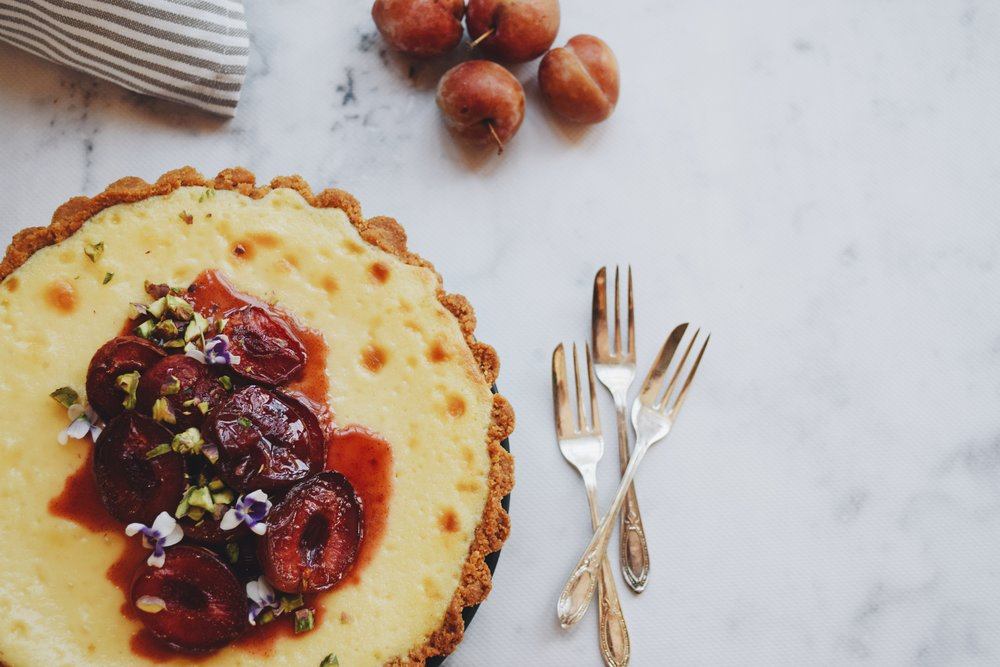 Baked vanilla cheesecake with roasted plums & native violets