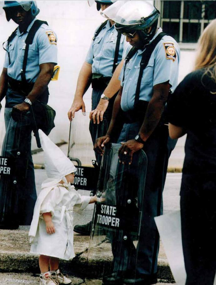 maggie-stiefvater: thesouthernthruway: unexplained-events: unexplained-events: This photo was taken over 20 years ago by Todd Robertson during a KKK rally in northeast Georgia. One of the boys approached a black state trooper, who was holding his riot shield on the ground. Seeing his reflection, the boy reached for the shield, and Robertson snapped the photo. I think the officer's expression says it all. This child standing before him is being taught how to hate even though he doesn't understand it. He probably doesn't understand the difference between this and Halloween. If any post on my blog gets really big, I hope it's this one. this is really fucking sad i think of everything we learn without even noticing I've been thinking about the expression on the officer's face since I saw this photo yesterday.
