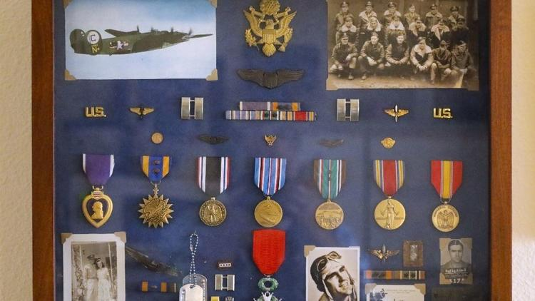 A framed collection of Alan Carlton's war-time memorabilia. (Howard Lipin/Union-Tribune)