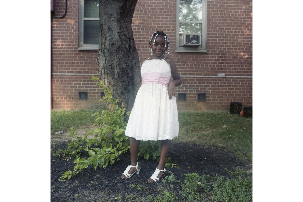 """You got a lot of great kids. Going to school, doing great things,"" says Herbie, an active member of the community who grew up here himself. This young girl was dressed up for her first grade graduation. First Street, Southwest D.C., June 2014"