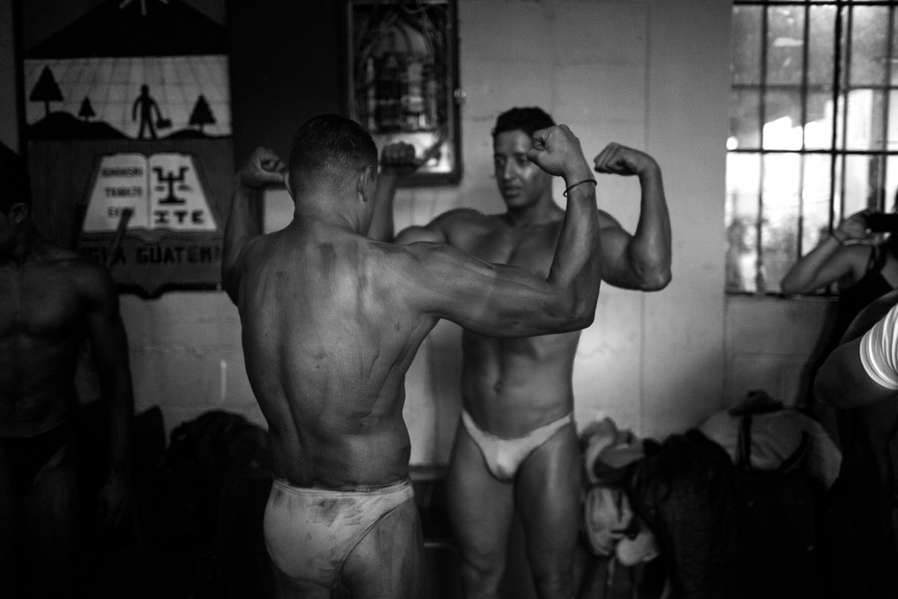 Competitors work on their poses before the Gimnasio La Fábrica bodybuilding contest in Antigua, Guatemala on July 19, 2014.