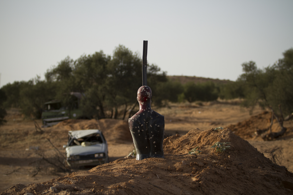 A silhouette designed for target practice is painted with the colors of the rebel flag and staked on top of a berm at a checkpoint, Kikla, Libya. July 18, 2011