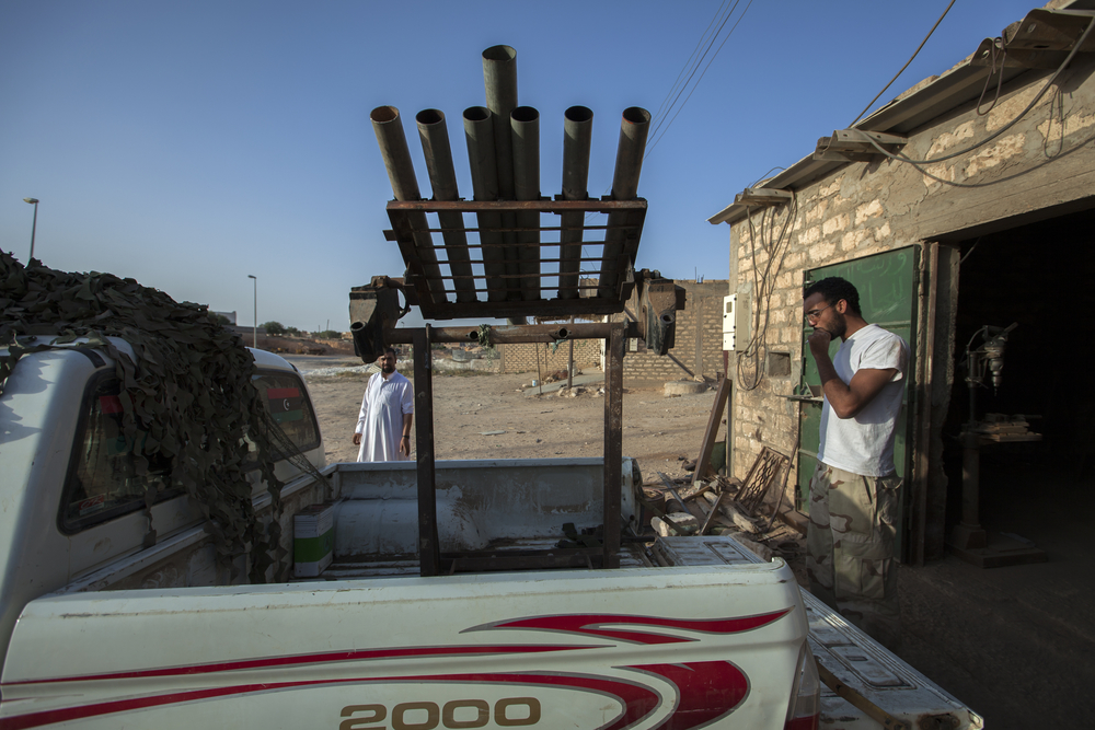 A mechanic who has repurposed his work to fabricate weapons platforms takes a break outside of shop in Zintan, Libya. July 18, 2011.