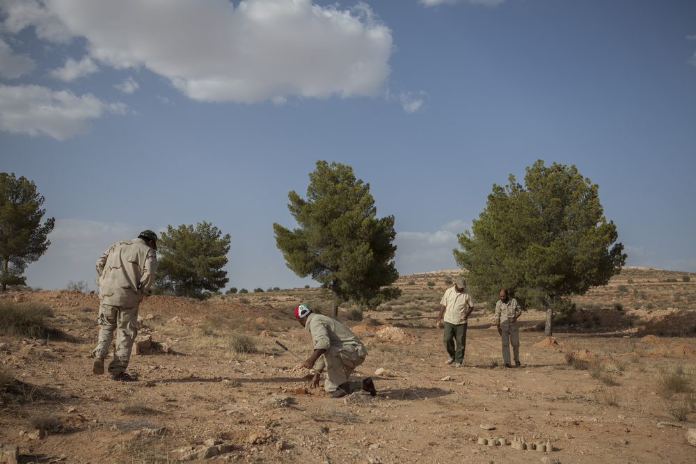 Milad Saadi (center, in red, white, and green hat), a former EOD technician in Gaddafi's army, leads a rebel de-mining team clearing T-AB-1 anti-personnel mines left by Gaddafi's forces.