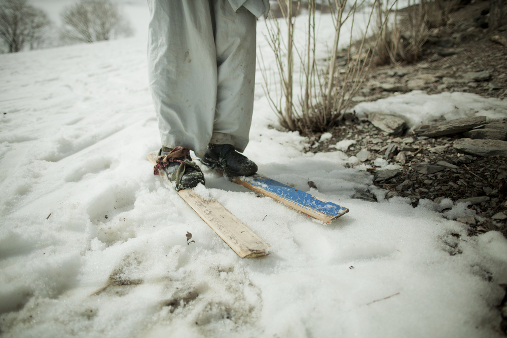Aref, a 16-year-old from the village of Jawzari, made his own skis from wood and old tin cans. Jawzari, Afghanistan. March 3, 2012.