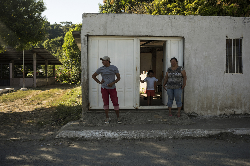 Danielo stands in front of the house where he is staying along with three other El Salvadoran refugees. Danielo would leave this house the next day after this woman's boyfriend showed up, drinking, and started acting violent with her and threatening him.