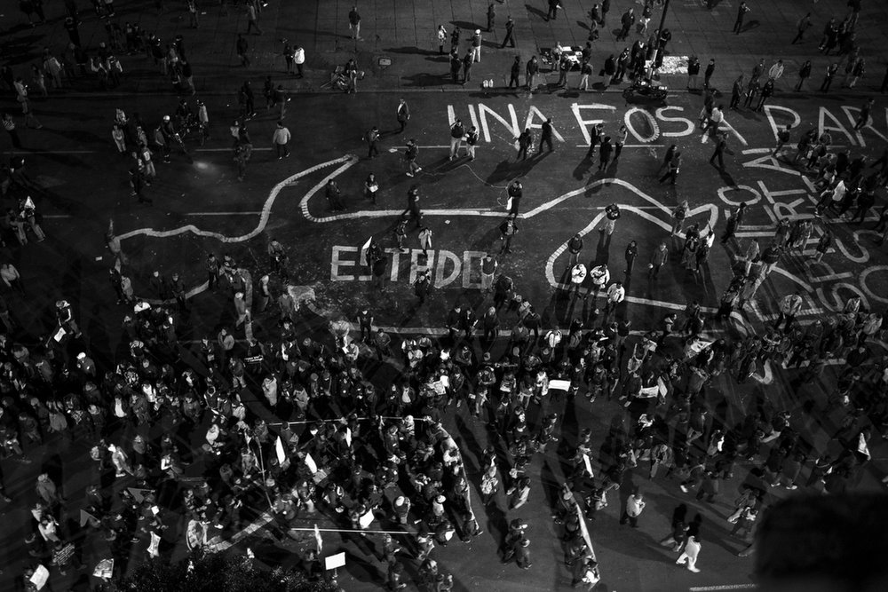 "Protesters demanded President Enrique Peña Nieto's resignation and chanted ""Vivos se los llevaron y vivos los queremos"" (They were taken alive, we want them alive). An outline of a corpse, labeled Estado (State), is painted on the road circling Mexico City's main plaza. The words above it read Una Fosa Para El Estado, (a grave for the state)."