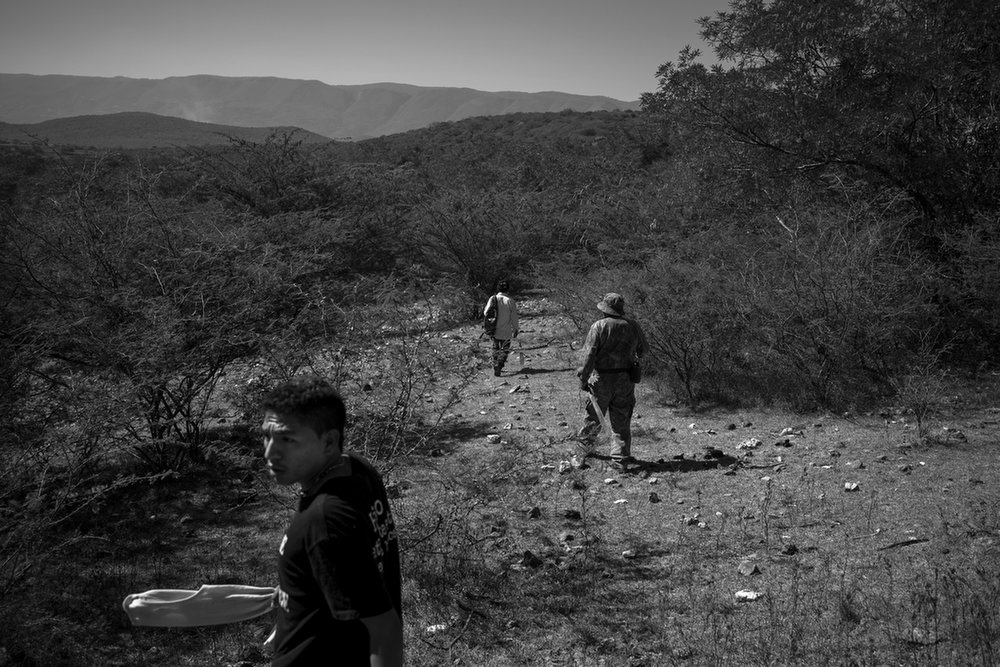 A group of volunteers walks through the hills looking for signs of graves or human remains during a civilian search party in Cocula, Mexico. December 5, 2014.