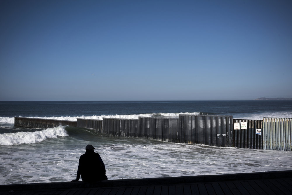 TIJUANA, MEXICO - NOVEMBER 18: A man sits overlooking U.S.-Mexico border  extending into the Pacific Ocean on November 18, 2016 in Tijuana. An estimated 4,000 Haitians are in Tijuana waiting for appointments with U.S. Customs and Border Protection but with unpredictable U.S. policies, Haitians don't know until the day of their appointment if they'll be allowed to stay in the U.S. or be deported.