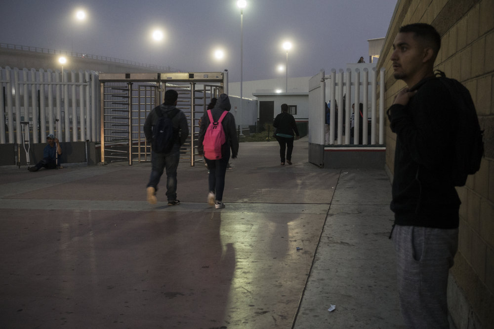 TIJUANA, MEXICO - MAY 2: Students in Tijuana walk towards the border crossing  into the United States early in the morning on May 2, 2017 in Tijuana, Mexico. Teachers in San Diego estimate that about 1000 students cross from Tijuana into the San Diego everyday to go to school.