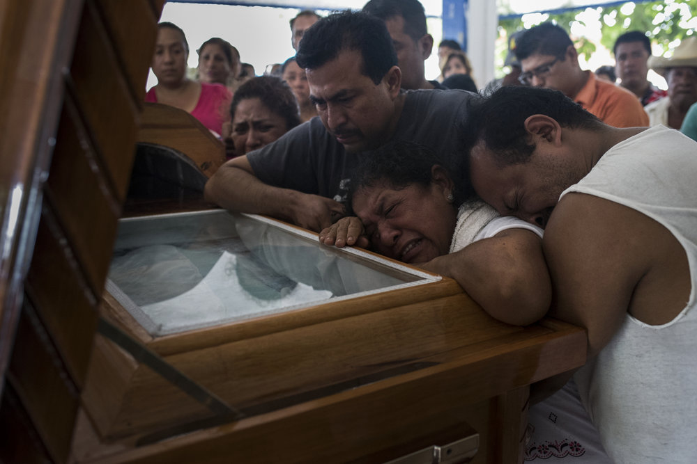 The family of Pedro Tamayo cry over his casket at his funeral on July 22, 2016 in Tierra Blanca, Veracruz.  Despite being under state sponsored protection, Tamayo was shot ten times in front of his house while his wife and children looked on. The Committee to Protect Journalists ranks Mexico as the sixth most dangerous country in the world for journalists and within Mexico, Veracruz is the most dangerous state for the profession.