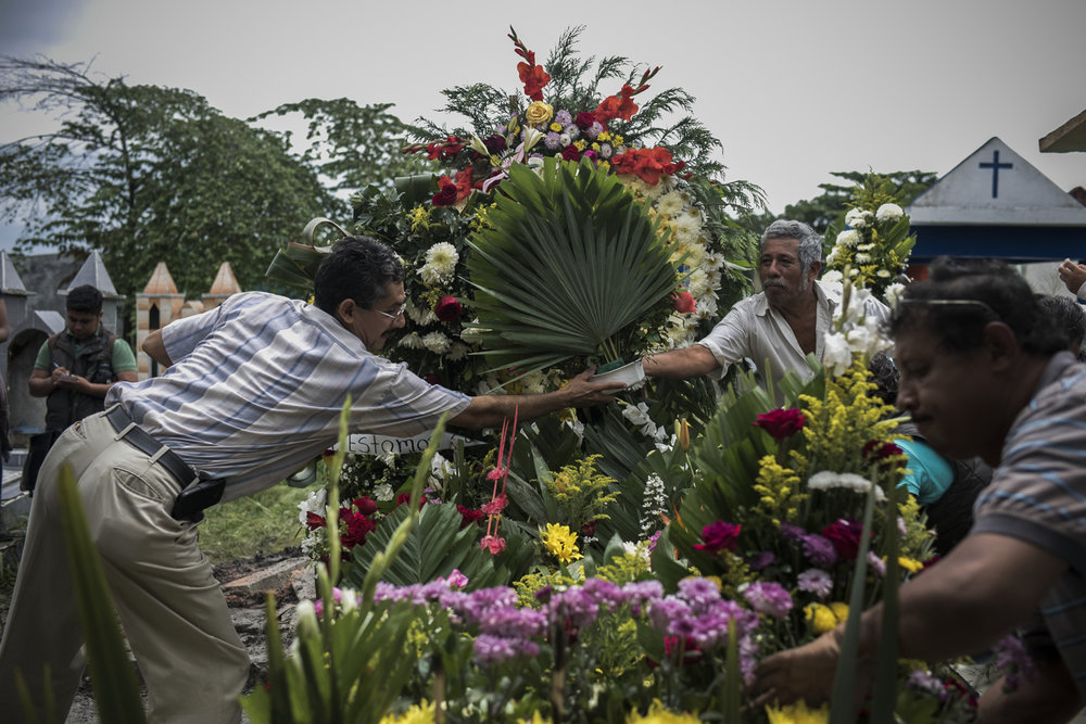 Pedro Tamayo's grave is covered with flowers after he is laid to rest at the cemetery on July 22, 2016 in Tierra Blanca, Veracruz.  Tamayo had reported on the abduction and murder of five young people by municipal police and as a result was under state protection. At the time of his murder a state police vehicle was reportedly parked near his house but did nothing to help.