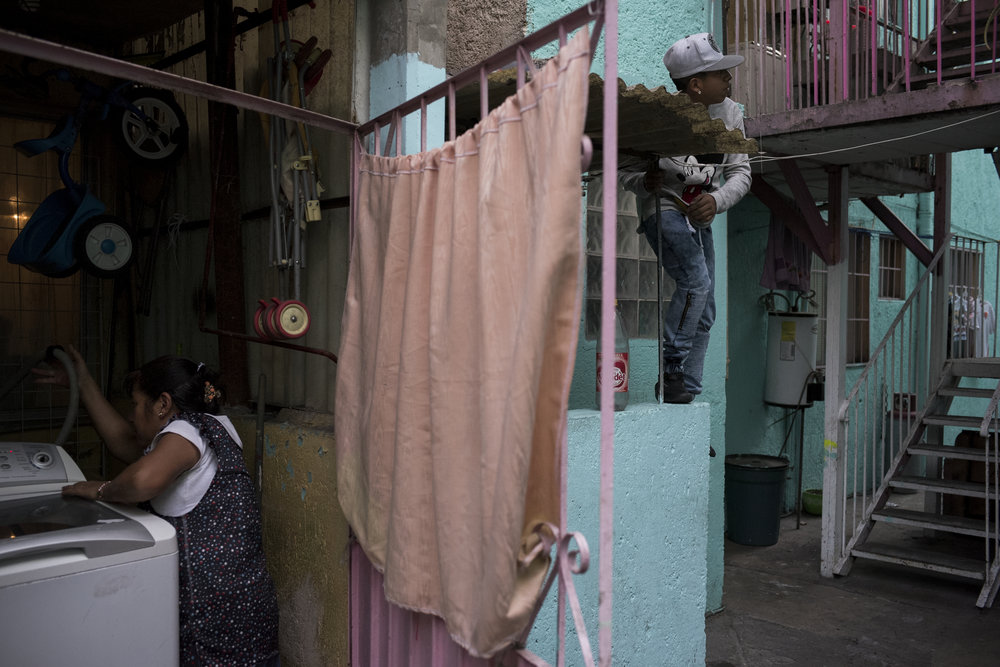 Fifteen year-old Pancho, an aspiring boxer from Morelos, climbs to get a better view of a barking dog in his apartment complex on February 28, 2017 in the Morelos neighborhood of Mexico City. Morelos is one of Mexico City's rougher neighborhoods and Pancho lives at home with his mom, dad, two sisters, and a niece in a small two room apartment.