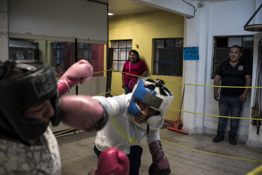 With Fifteen year-old Pancho, a boxer from Morelos, spars with a fellow boxer while her parents watch from the side on February 28, 2017 in the Tepito neighborhood of Mexico City. Pancho has struggled to stay in school and his coach hopes boxing can offer a source of discipline and distraction from the gangs and drugs which surround Pancho everyday.