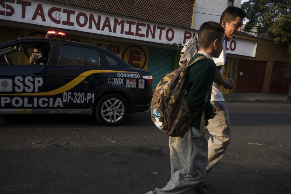 Pancho, a fifteen-year-old boxer, walks to school with a neighbor and classmate on March 3, 2017 in the Morelos neighborhood of Mexico City. Morelos is one of Mexico City's rougher neighborhoods where gangs and drugs are a constant threat for young teenagers.