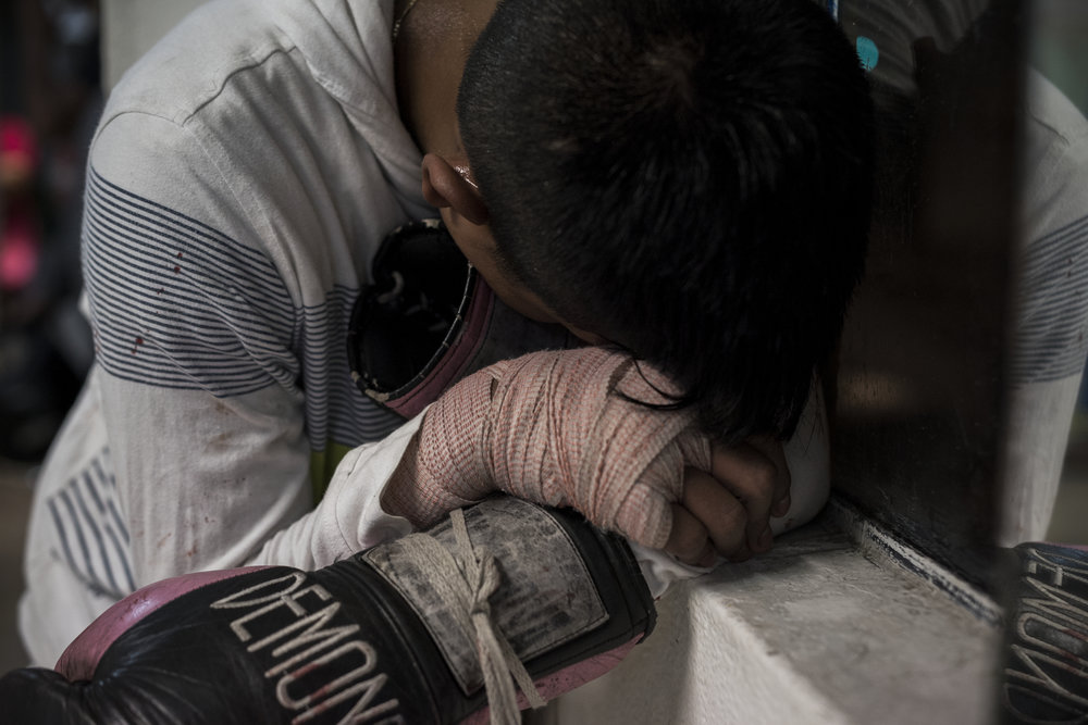 Fifteen year-old Pancho, a boxer from Morelos, rests after two rounds of sparring on February 28, 2017 in the Tepito neighborhood of Mexico City. Pancho has been boxing for only four months but his coach sees potential and hopes he will compete in Mexico's golden glove tournament.